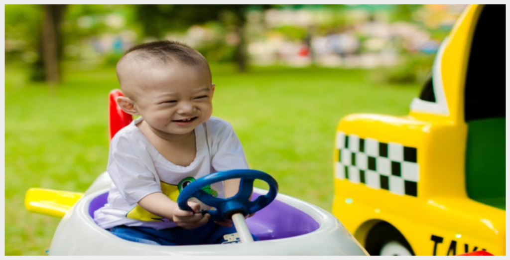 Baby riding toy car in play area